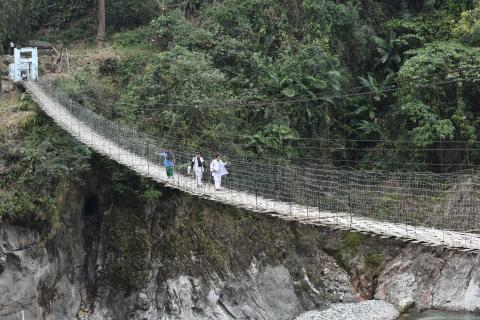 Two women cross a very high and narrow bridge across a river.