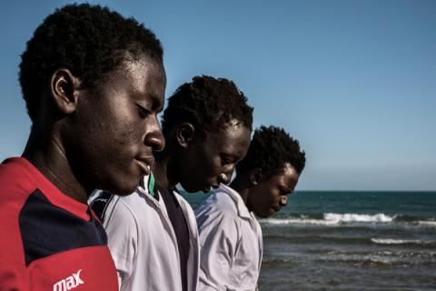 A Gambian group of boys survey the ocean from the beach
