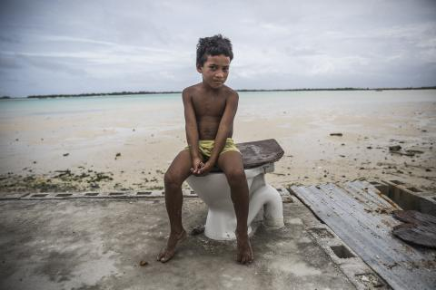 A boy sits on an abandoned toilet near a destroyed family home, Fiji