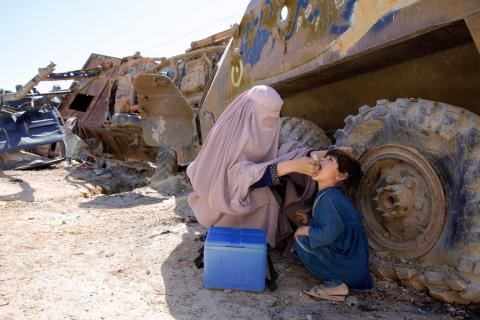 A young boy gets inoculated beside a tank
