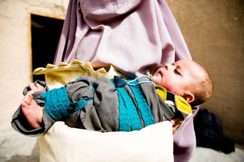 A woman holds a sleeping baby, Afghanistan