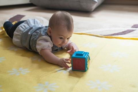 A baby playing with a cube