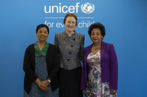 Three women stand in front of a UNICEF logo