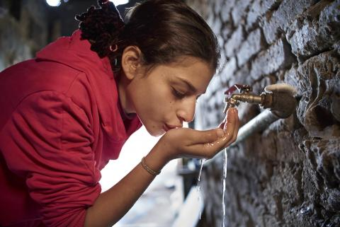 A girl drinks water from a tap