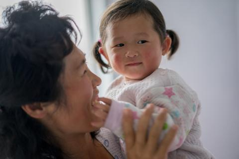 A woman smiles at her baby, DPR Korea