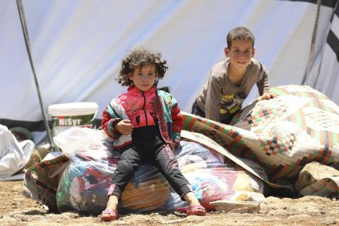 Children sit on piles of textiles, Syrian Arab Republic