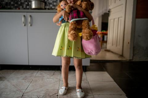 Four-year-old Mirjeta (name changed) holds her toys while getting ready to go out with her mother in Tirana, Albania, in June 2018. Mirjeta's mother was physically and mentally abused by her husband, who became violent after discovering that she was pregnant with a girl.