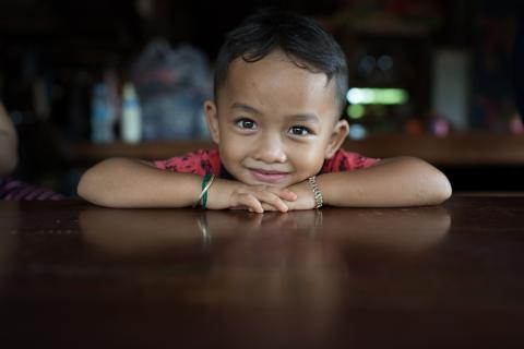 A four-year-old boy rests his head on his hands at a table in his house, smiling.
