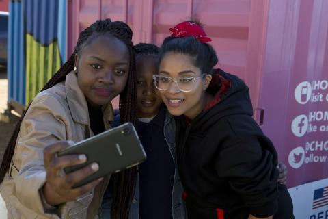 A group of teenage girls look at a cellphone, South Africa