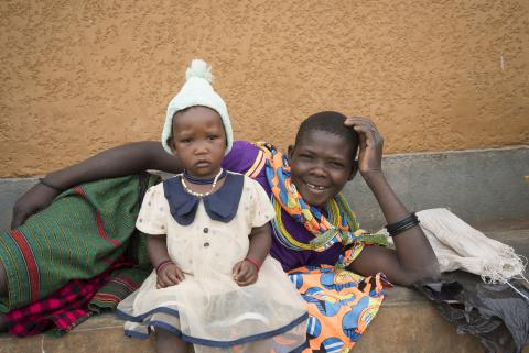 A mother lies on her side, head in hand, with her baby seated in front of her outside a health centre in Uganda.