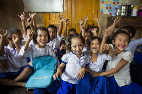Myanmar. Children in a classroom smile for the camera.