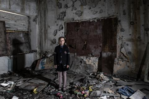 A girl stands in a damaged classroom in Ukraine