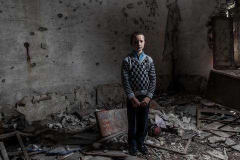 A child stands in the remains of a classroom in eastern Ukraine.