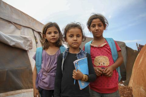 Three girls in backpacks stand outside a tent school in a makeshift camp in the Syrian Arab Republic.