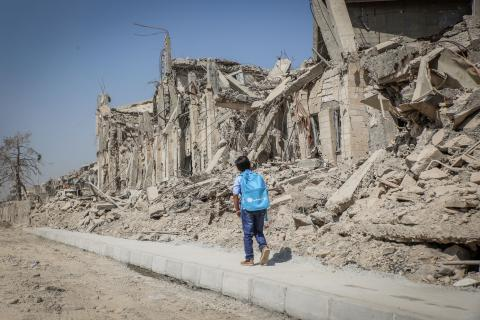 A child walks past damaged buildings in Iraq.