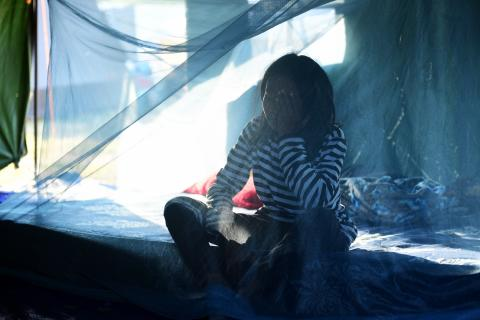 Indonesia earthquake and tsunami. A displaced girl sits on a mattress in her temporary shelter.