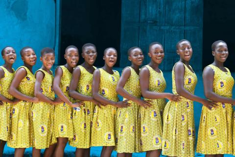 A group of schoolgirls in Ghana who are all wearing matching dresses stand in a line behind each other