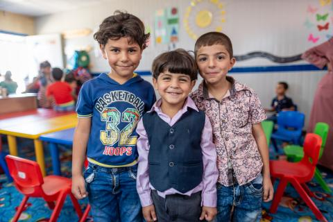 Three young students stand smiling in their classroom in Jordan.