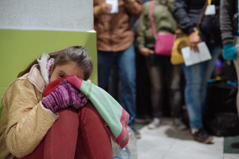 A girl waits in a line of people waiting to enter Ecuador.