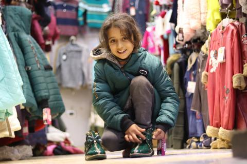 Eight-year-old Rana in Aleppo, Syria, tries on a matching winter jacket and shoes.
