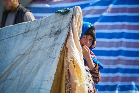 Afghanistan. A child stands by a tent.