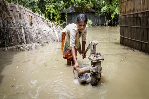 During the 2016 floods in Kurigram, northern Bangladesh, a girl tries to pump clean water from a standpipe.