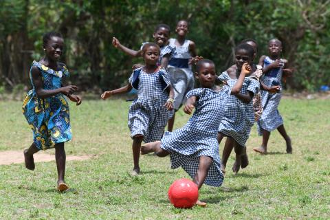 Girls in blue school uniforms play football in the grass.
