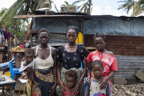 Mozambique. A family stands in front of a shelter.