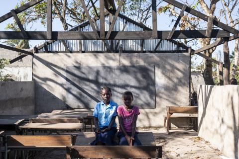 Mozambique. Two children sit in a damaged classroom in Beira, Mozambique.