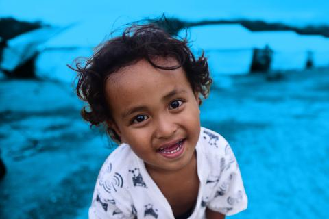 A four-year-old leans in and smiles in front of temporary housing in Indonesia in 2018.