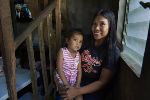 A woman holds her daughter on her lap, Philippines