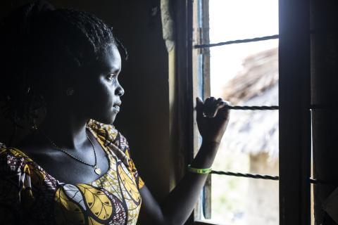 A young woman looks out the window of her home in Uganda.
