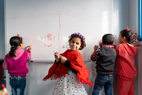 A six-year-old girl in Jordan stands at a whiteboard in her kindergarten class, smiling over her shoulder.