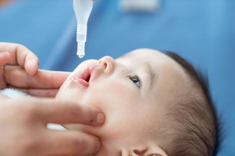 A one-month-old receives an oral vaccination.