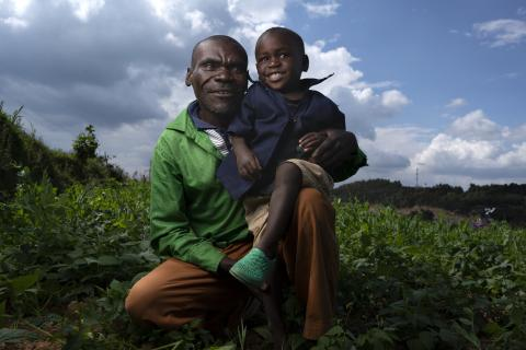 A father squats with his two-year-old son in his lap, both smiling, in a field in Rwanda.