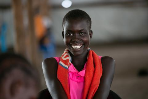 A young woman in colourful attire smiles brightly at the camera.