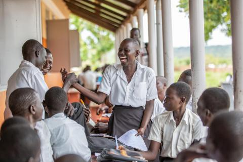 A 17-year-old girl laughs with friends outside their school in Uganda, 2019.
