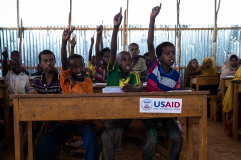 Young students raise their hands during class in Somalia.