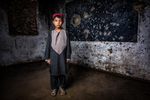 Afghanistan. A child stands in a damaged classroom.