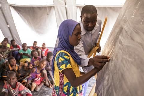 Mali. A child and her teacher work on a blackboard.