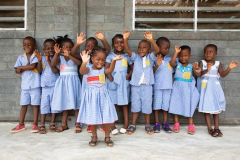 Young children in blue uniforms stand outside a preschool made of plastic bricks in Côte d'Ivoire, waving their arms.
