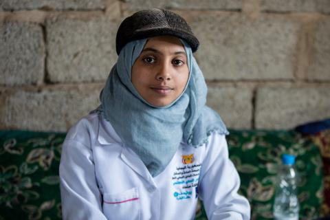 An adolescent community health worker in her medical jacket poses for a photo.