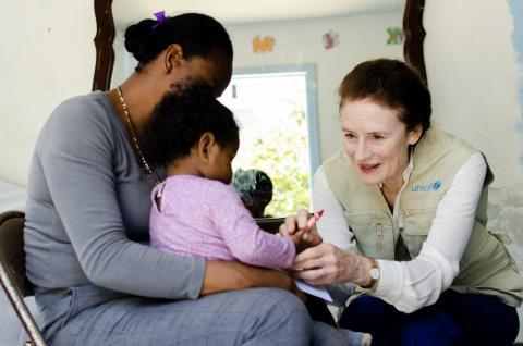 UNICEF Executive Director Henrietta Fore speaks with a mother and her one-year old child