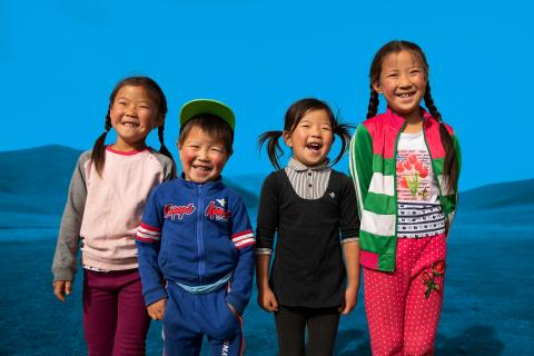 Four children standing side-by-side in Mongolia laugh outdoors.
