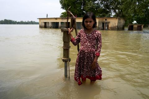 A girl stands in front of her school in Bangladesh that has been submerged under water. The well she stands upon is the only source of clean water in the area.