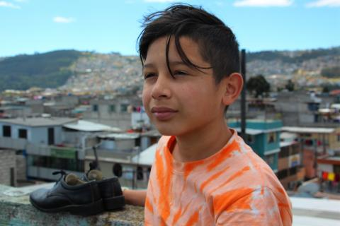 Ecuador. A boy stands next to a pair of shoes his classmates helped to pay for.