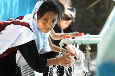 Afghanistan. A girl washes her hands.