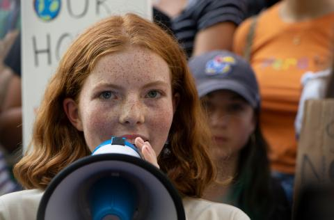 New York City: a girl speaks into a loud speaker at a climate action demonstration.