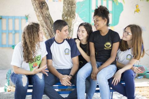 Five teenagers chat on a bench outside in Brazil.