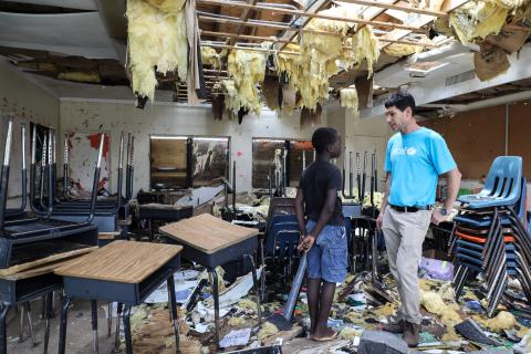 A boy talks with a UNICEF worker in his totally destroyed classroom.